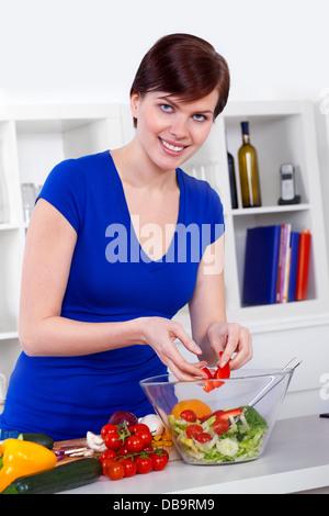 junge Frau, die Zubereitung gesunden Salat in der modernen Küche - Stockfoto