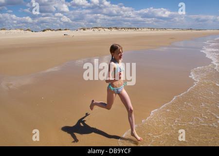 Mädchen am Strand in Richtung Meer in Cabanas de Tavira, Algarve, Portugal. Ihr Name ist Irene, sie ist 8 Jahre - Stockfoto