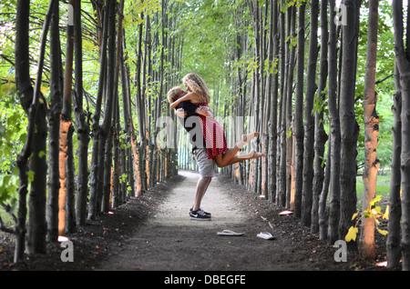 Ein junges Paar in den Wald, ein junger Mann romantisch holt und schmiegt sich an eine junge Frau in eine Reihe - Stockfoto