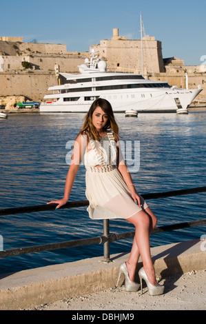 Eine junge Frau ruhen auf dem Zaun schützt Passanten vor dem Absturz in Dockyard Creek, Malta. Ein super-Yacht ist - Stockfoto
