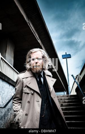 Bärtiger Mann in Anzug und Mantel walking Treppen hinunter in eine u-Bahn. - Stockfoto