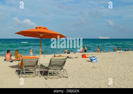 Strandkörbe, orange Sonnenschirm und viele glückliche Strandurlauber in South Beach, Miami, Florida.  Ein Kreuzfahrtschiff - Stockfoto