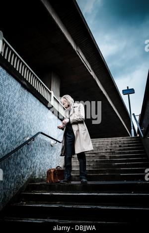 Bärtiger Mann in Anzug und Mantel hält eine alte Aktentasche aus Leder walking Treppen hinunter in eine u-Bahn. - Stockfoto