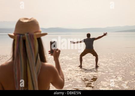 Kroatien, junge Frau am Strand fotografieren - Stockfoto