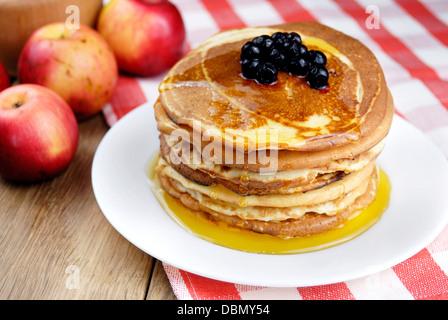 Stapel von Pfannkuchen mit Beeren in die weiße Platte auf dem Holztisch - Stockfoto