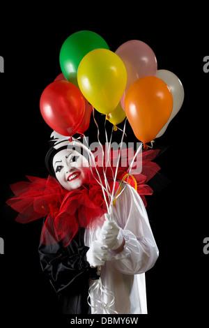 Glücklich weiblicher Pierrot Clown mit bunten Luftballons - Stockfoto