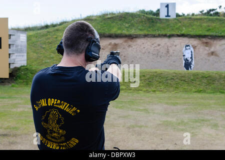 Ballykinlar, Nordirland. 2. August 2013 - ein Mann trägt ein t-Shirt Spezialoperationen feuert eine Glock 19 Pistole - Stockfoto