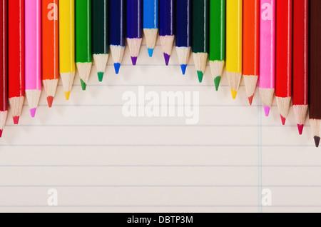 Farbstiften in Folge gegen leichte gelbe Notizbuch Papier - Stockfoto
