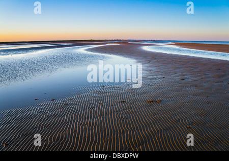 Das Wellenmuster auf dem Sand war sanft beleuchtet, wenn die Sonne in Bolivar-Halbinsel in Texas untergeht. - Stockfoto