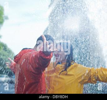 Glückliche Paare tanzen im Regen Stockfoto