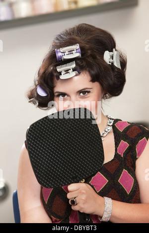 Frau in Lockenwickler hinter Spiegel - Stockfoto