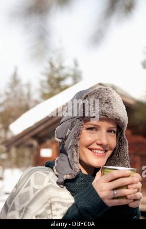 Porträt der Frau in Pelzmütze Kaffeetrinken Außenkabine hautnah - Stockfoto