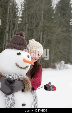 Glückliche Frau umarmt Schneemann in Wäldern - Stockfoto