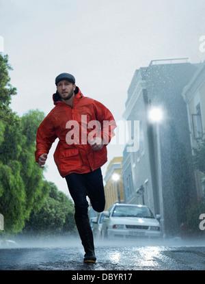 Mann im Regenmantel laufen im Regen - Stockfoto