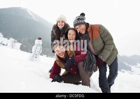 Porträt der happy Friends in schneebedeckten Feld mit Schneemann - Stockfoto