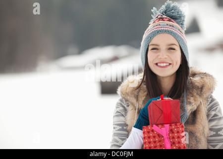 Porträt der lächelnde Frau mit Weihnachtsgeschenken in schneebedecktes Feld - Stockfoto