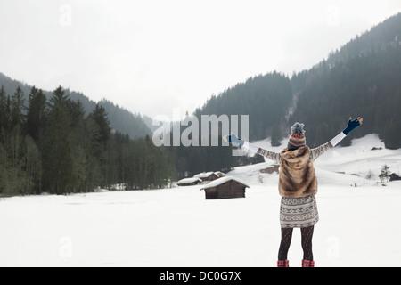 Unbeschwerte Frau mit ausgestreckten in schneebedecktes Feld - Stockfoto
