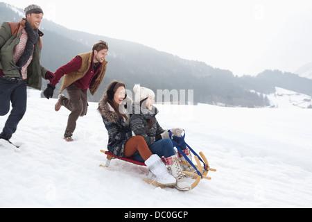 Begeisterte Freunde Rodeln in schneebedecktes Feld - Stockfoto