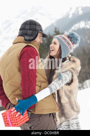 Frau für Weihnachtsgeschenk hinter Mann zurück in schneebedeckten Feld erreichen - Stockfoto