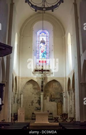 Glasfenster und Kreuz in der hoch und schmal Kirche Saint-Nicolas in Trémolat, Dordogne, Nouvelle-Aquitaine im Südwesten - Stockfoto