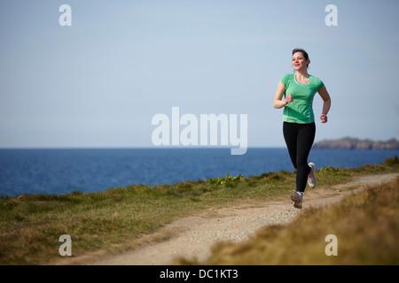 Junge Frau, die entlang der Küste entlang - Stockfoto
