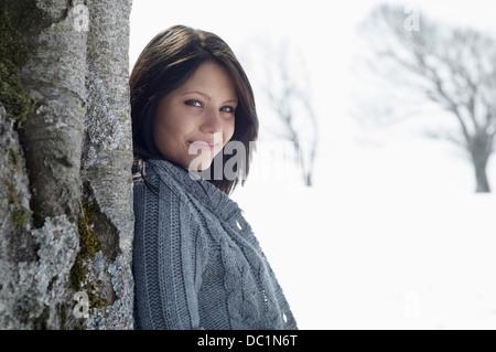 Junge Frau gelehnt Kahler Baum im schneebedecktes Feld - Stockfoto