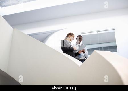 Unternehmer und Unternehmerin mit digital-Tablette auf moderne Treppe - Stockfoto