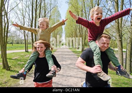Mutter und Vater racing mit zwei jungen auf Schultern durch den park - Stockfoto