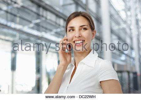 Junge Geschäftsfrau mit Handy, Lächeln - Stockfoto