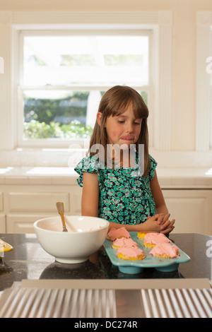 Junges Mädchen Blick auf Muffins, Lippen lecken - Stockfoto