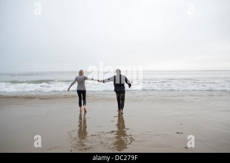 Älteres Paar halten die Hände am Strand - Stockfoto