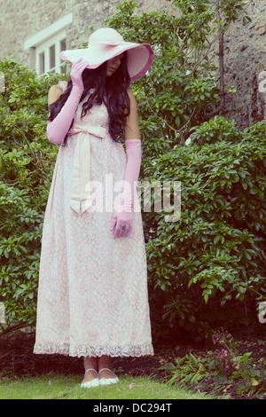 eine schöne Frau in einem rosa Kleid mit einem Sonnenhut steht vor einer Hütte - Stockfoto