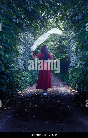 eine Frau in einem roten Kleid ist Fuß durch den Wald mit einem weißen Schal - Stockfoto