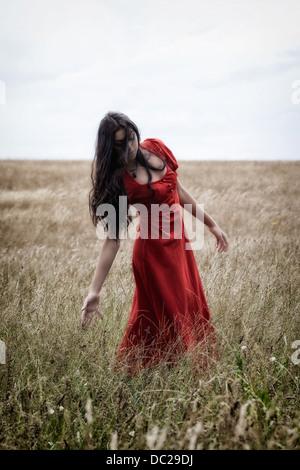 eine Frau in einem roten Kleid auf einem Feld, das Spiel mit dem Korn - Stockfoto
