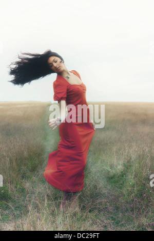 eine Frau in einem roten Kleid tanzt auf einem Feld - Stockfoto