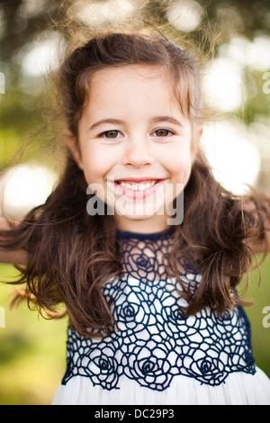 Porträt eines Mädchens mit langen braunen Haaren, Blick in die Kamera - Stockfoto