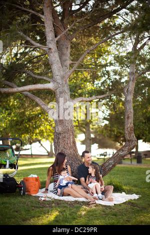 Familie mit zwei Kindern sitzen auf der Picknickdecke unter Baum - Stockfoto