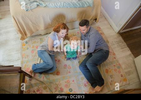 Paar mit Kind am Boden liegend - Stockfoto