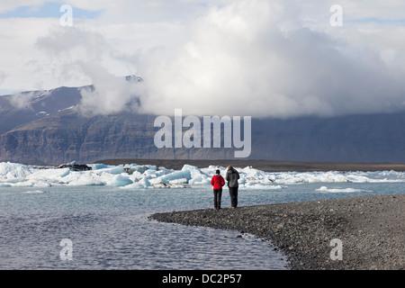 Zwei Personen genießen Sie die Aussicht über die Jökulsárlón Gletscher Vatnajökull-Nationalpark Lagune Island - Stockfoto