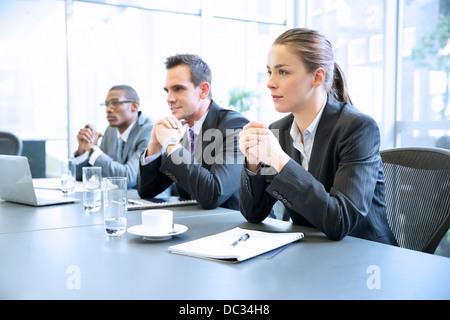 Aufmerksame Geschäftsleute mit den Händen umklammert in treffen - Stockfoto