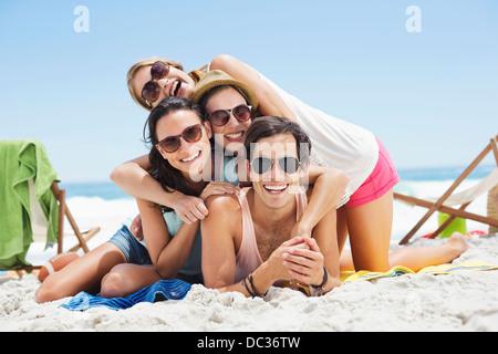 Porträt der happy Friends Verlegung übereinander am Strand - Stockfoto