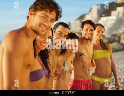 Porträt der happy Friends in einer Reihe am Strand - Stockfoto
