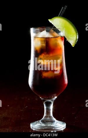 Cuba Libre, Rum und Cola cocktail serviert in einem Stamm-Glas mit einer Kalk-Garnitur - Stockfoto