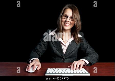 Attraktiven jungen professionellen corporate Frau saß hinter ihrem Schreibtisch mit Computer-Tastatur und Maus. - Stockfoto