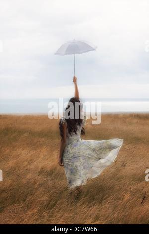 ein Mädchen in einem geblümten Kleid auf einem Feld mit einem Sonnenschirm Stockfoto