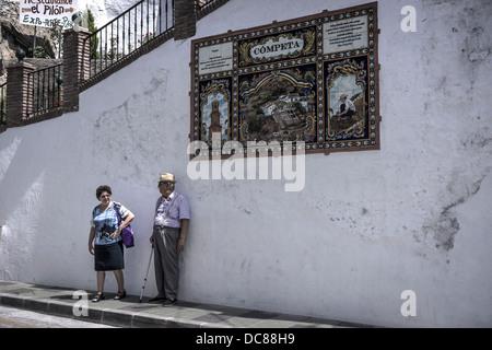 Zwei Bewohner von Competa chat unter eines der gefliesten Zeichen, die in der weiß getünchten andalusischen Stadt - Stockfoto