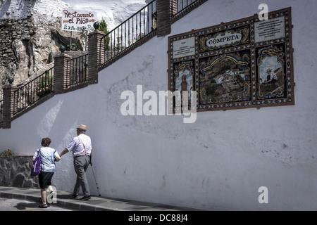 Zwei Bewohner von Competa gehen vorbei an eines der gefliesten Zeichen, die in der weiß getünchten andalusischen - Stockfoto