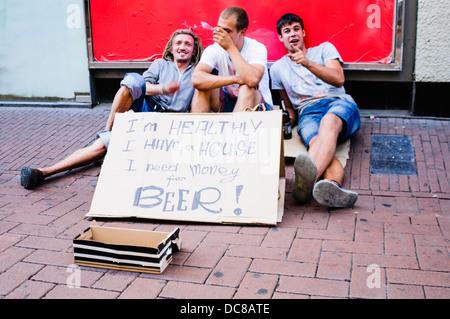 """Drei Männer betteln um Geld mit Schild mit der Aufschrift """"Ich bin gesund, ich habe ein Haus. Ich brauche Geld für - Stockfoto"""