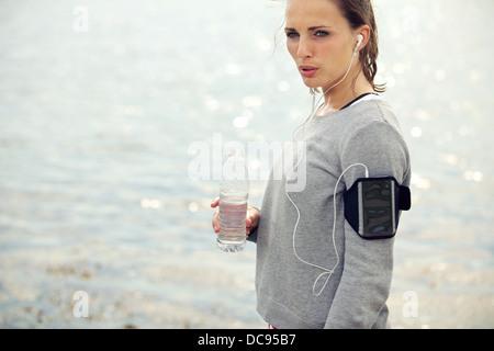 Weibliche Läufer suchen ernsthafte halten Sie ein Flasche Wasser - Stockfoto