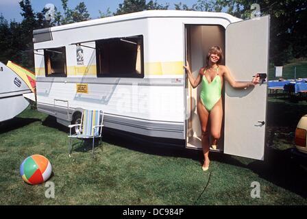 Eine junge Frau im Badeanzug präsentiert sich in einem neu vorgestellten Wohnwagen, fotografiert im August 1986. - Stockfoto
